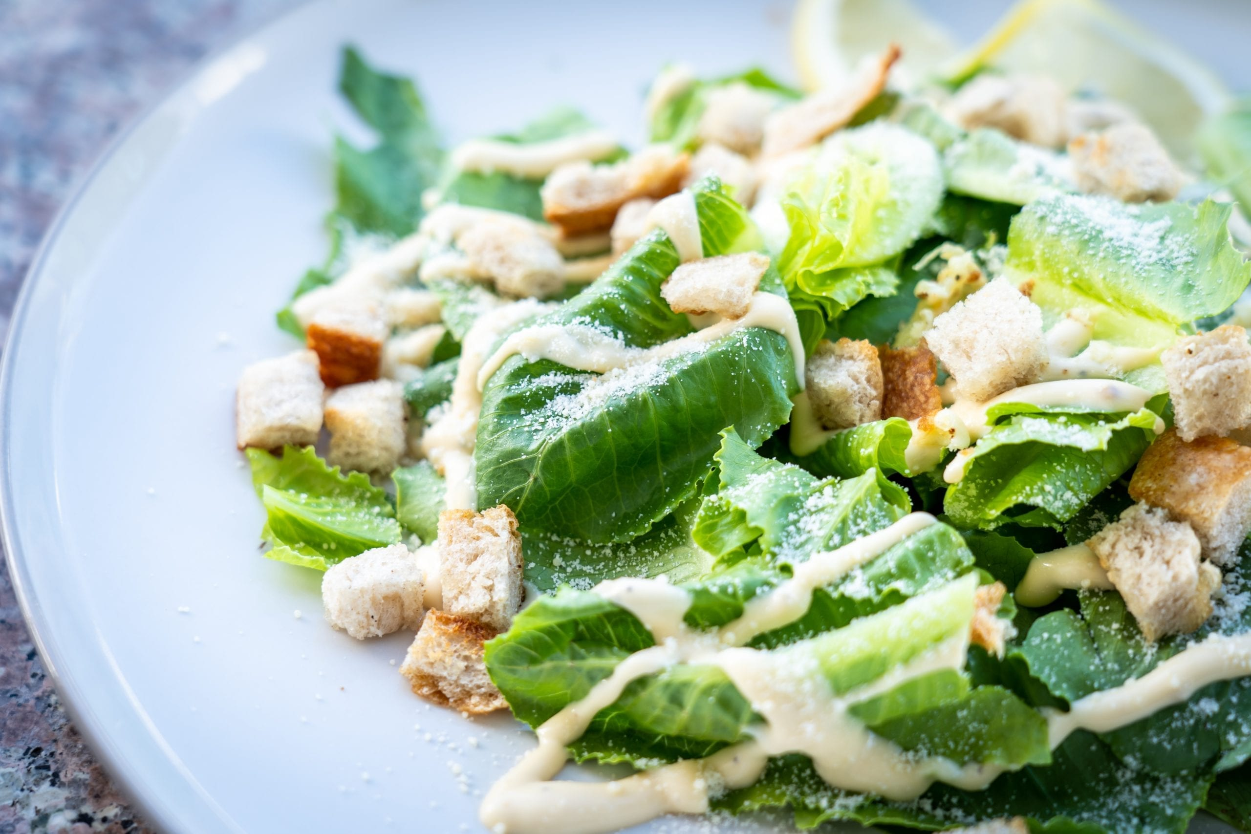 Caesar salad with croutons, romaine lettuce, Parmesan cheese, and Caesar dressing drizzled on top