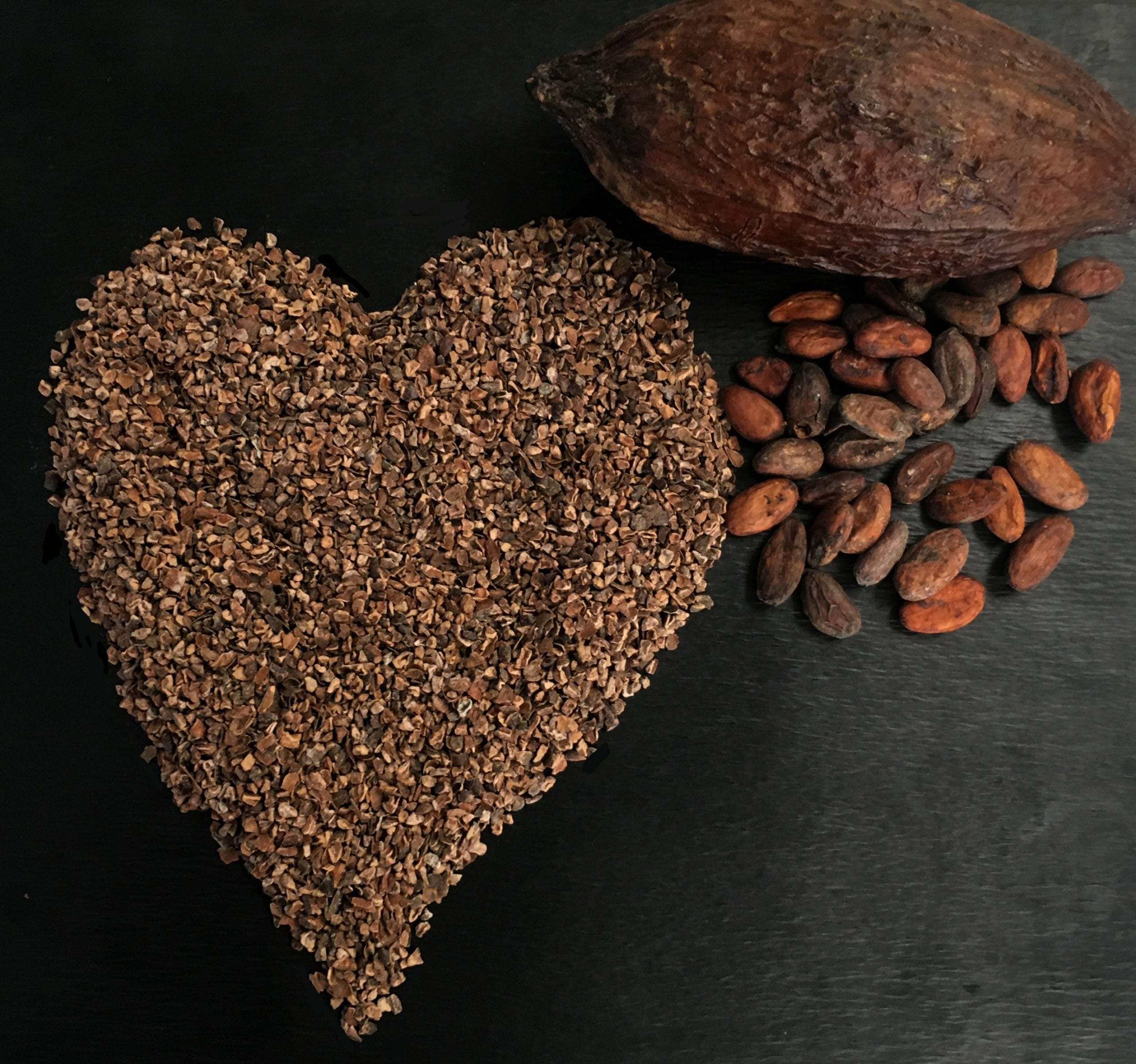 Cocoa beans next to ground up cocoa beans in the shape of a heart